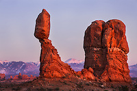 Balanced rock glow red with the last light of day, La Sal mountains in the background, Arches National Park, Utah