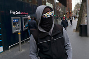 Man wearing a black mask across his face and sunglasses with cartoon eyes printed on the lenses, concealing his identity in London, England, United Kingdom.