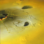 An active volcanic eruption on Jupiter's moon Io was captured in this image taken on February 22, 2000 by NASA's Galileo spacecraft. Tvashtar Catena, a chain of giant volcanic calderas cantered at 60 degrees north, 120 degrees west, was the location of an energetic eruption caught in action in November 1999. A dark, 'L'-shaped lava flow to the left of the centre in this more recent image marks the location of the November eruption. White and orange areas on the left side of the picture show newly erupted hot lava, seen in this false colour image because of infrared emission. The two small bright spots are sites where molten rock is exposed to the surface at the toes of lava flows