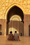 Rear view of people sitting and kids playing in front of Hassan II Mosque in Casablanca, Morocco