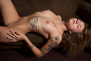 Beautiful reclining nude woman on brown sofa with many exotic tattoos on her body