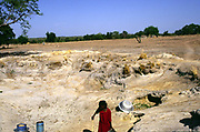 Asumpaheme, who is blind, collects water at a water hole She is blind due to the entirely preventable 'River Blindness' (Onchocerciasis) Despite herhandicap, she has no choice but to continue farming.