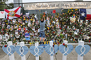 A man places a rosary at the Surfside Wall of Hope & Memorial, on Saturday, July 10, 2021, in honor of those who lost their lives at the 12-story oceanfront condo, Champlain Towers South, that collapsed in Surfside.