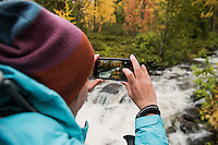 Female hiker takes photo of flowing river with smart phone, Kungsleden trail, Lapland, Sweden