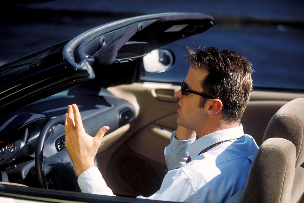 Young Anglo businessman in convertable uses his cell phone while in urban traffic in Austin, Texas.  Model Release.<br /> ©Bob Daemmrich