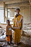 A mother and son stand on building site outside the crèche of the Veera Desai Centre, Mumbai.  The centre is 1 of 70 crèche's in India run by the Mumbai Mobile Crèche organisation.