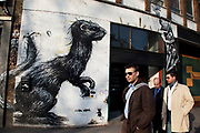 Roa weasel on Great Eastern Street in Shoreditch, East London. Standing next to works by Ben Eine (coloured letterform 'E') and Phlegm's bizarre character.  Roa is a Belgian street artist renowned for his giant black and white animals which can be found on walls and shutters in varying states of decay. Biggest of them all is the Roa Crane on Hanbury Street which was put up in 2010. There are also a few Rats and Birds which reside on shop shutters along Brick Lane.<br /> <br /> Street art in the East End of London is an ever changing visual enigma, as the artworks constantly change, as councils clean some walls or new works go up in place of others. While some consider this vandalism or graffiti, these artworks are very popular among local people and visitors alike, as a sense of poignancy remains in the work, many of which have subtle messages.