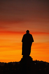 George Washington Statue in Silhouette overlooking Seattle at sunset from the campus of the University of Washington, Seattle, Washington, US.