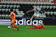 Swansea city's Jonjo Shelvey jumps over Oriol Romeu of Valencia. UEFA Europa league match, Swansea city v Valencia at the Liberty Stadium in Swansea on Thursday 28th November 2013. pic by Andrew Orchard, Andrew Orchard sports photography,