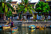 Aug 2017, Hoi An: Sunset at the docks with small boats and a man bringing in a dingy