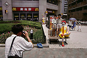 Children pose with Ronald MdDonald outside a McDonald's restaurant in the Pudong area of Shanghai. Shanghai, China.