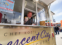 Chris Kozlowski of Chef Coz's Crescent City Kitchen Food Truck calls out for #58 an order of Ropa Vieja Cuban Po' Boy sandwich during the Exit 20 Food Truck Festival at Tanger Outlet on Saturday.  (Karen Bobotas/for the Laconia Daily Sun)