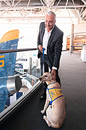 Garden City, New York, USA. June 21, 2018. NASA space shuttle astronaut MIKE MASSIMINO poses with dog from Canine Companions for Independence, a Medford organization, brought by Volunteer Puppy Raiser Florence Scarinci, after the museum's Members Meet & Greet before Massimino's free lecture in JetBlue Sky Theater Planetarium at the Cradle of Aviation's Museum, part of the museum's Countdown to Apollo at 50, celebrating 50th anniversary of Apollo 11 moon landing on July 20, 1969.
