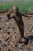 AREKJ1 Child playing in mud pool