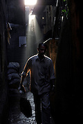 Sunlight pierces the narrow alleys of the slum as a man makes his way to work in the early morn.