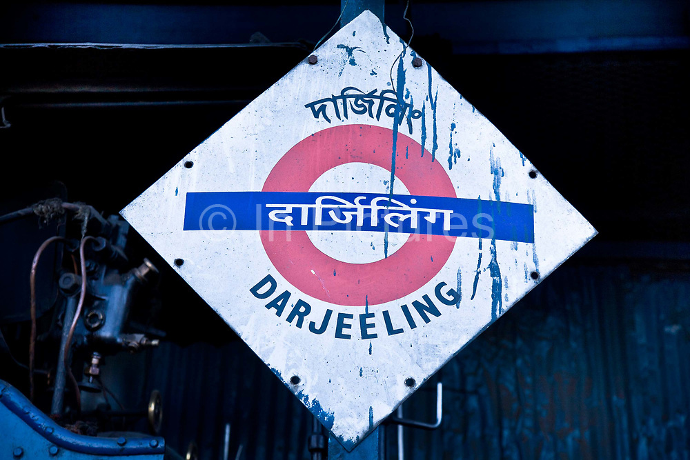 """Darjeeling train station sign. The Darjeeling Himalayan Railway, nicknamed the """"Toy Train"""", is a narrow-gauge railway from Siliguri to Darjeeling in West Bengal, run by the Indian Railways. It was built between 1879 and 1881 and is about 86 km long. The elevation level is from about 100 m at Siliguri to about 2200 m at Darjeeling. It is still powered by a steam engine and travels daily between the two towns, as well as a shorter route to Kurseong.  It is now classed as a World Heritage Site by UNESCO. India."""