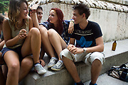 Teenagers sit by the fountain in the Piazza Independenza, Verona, Italy
