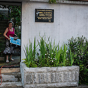 MOSTAR, BOSNIA AND HERZEGOVINA - JUNE 28:  Majka a mother who lost her twenty years old daughter Sunita during the 1993 siege stands next to the plaque remembering her on June 28, 2013 in Mostar, Bosnia and Herzegovina. The Siege of Mostar reached its peak and more cruent time during 1993. Initially, it involved the Croatian Defence Council (HVO) and the 4th Corps of the ARBiH fighting against the Yugoslav People's Army (JNA) later Croats and Muslim Bosnian began to fight amongst each other, it ended with Bosnia and Herzegovina declaring independence from Yugoslavia.  (Photo by Marco Secchi/Getty Images)