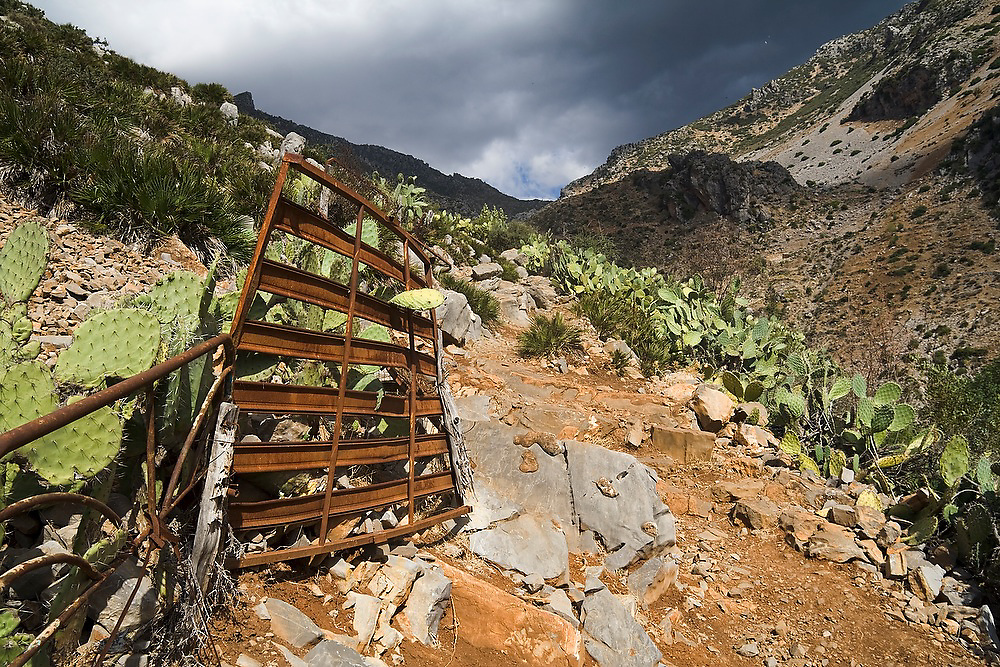 A rusty gate lies along a path lined with prickly pear cacti in Talassemtane National Park, in the Rif Mountains, just outside the city of Chefchaouen, Morocco. The cacti, planted by the local goat herders, help restrain the animals to the trail.