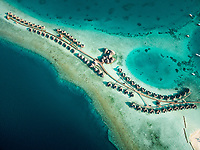 Aerial view above a group of bungalows in a luxury resort, Maldives island.