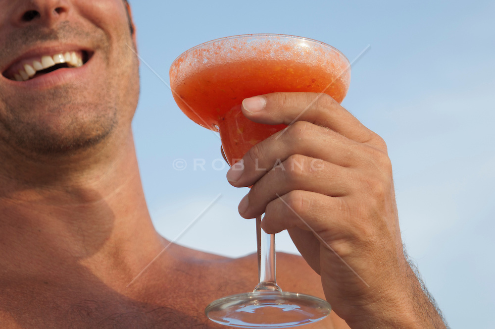 man on vacation having a frozen margarita