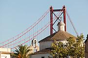 The Ponte 25 de Abrel bridge stands tall behind the Santo Amaro Chapel in Lisbon, Portugal