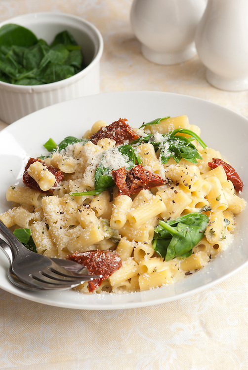 Sundried tomato and spinach pasta topped with grated Parmesan