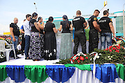 """The route from Florin Cioba's home to the cemetery - there are crowds of people. Many people, onlookers Gypsy and not line the streets, watching from windows and the pavement. The hearse is surrounded by security.<br /> <br /> Florin Ciaoba's funeral and the crowning of two kings. Daniel and Dorian were crowned, Danile with the bigger crown is King of Romanian Roma Gypies whilst his older Brother Dorian has the smaller crown and is King of Gypsies of the world and deals with foriegn affairs. His hearse (a lorry) packed with security guards is taken from The Cioaba family home to the cemetery<br /> <br /> Florin Tănase Cioabă (1954 – 18 August 2013) was a Romanian Romani Pentecostal minister and self-proclaimed """"King of Roma around the world"""". He died on 18 August 2013 of cardiac arrest at Akdeniz Üniversitesi in Antalya. He was 58 years old.<br /> <br /> In September 2003, Florin Cioaba sparked controversy when he married his 12 year-old daughter Ana-Maria to Mihai Bitrita, a Roma boy aged 15. However, following the wave of criticism, he promised to work to uproot the tradition of child marriages among the Roma. Florin Cioaba also encouraged Roma families to send their children to school during his attempt to fight poverty resulting from a lack of education.<br /> <br /> Cioaba was elected president of the International Romani Union in April this year"""