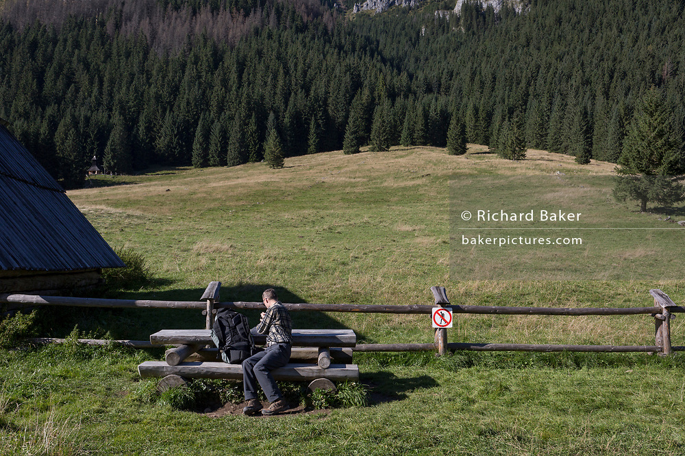 A walker rests with a background of spruce trees and the meadows of a farm where hikers are discouraged from crossing over wooden agricultural fencing in Dolina Chocholowska, a hiking route in the Polish Tatra mountains, on 17th September 2019, near Zakopane, Malopolska, Poland.