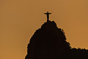 Christ the Redeemer statue silhouetted at sunset on Corcovado Mountain in Rio de Janeiro, Brazil.