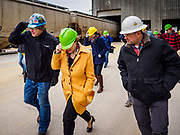 12 APRIL 2019 - NEVADA, IOWA: CHRIS CLEVELAND, Production Manager of Lincolnway Energy, (left), US Senator AMY KLOBUCHAR, (D-MN) and MIKE HOLLENBERG, CEO of Lincolnway Energy, (right), walk against the wind during a tour of the Lincolnway Energy ethanol plant in Nevada, IA. Winds in the area gusted over 40MPH Friday. Sen. Klobuchar is touring Iowa this weekend to support her bid for the Democratic nomination of for the US Presidency. Iowa traditionally hosts the the first election event of the presidential election cycle. The Iowa Caucuses will be on Feb. 3, 2020.            PHOTO BY JACK KURTZ