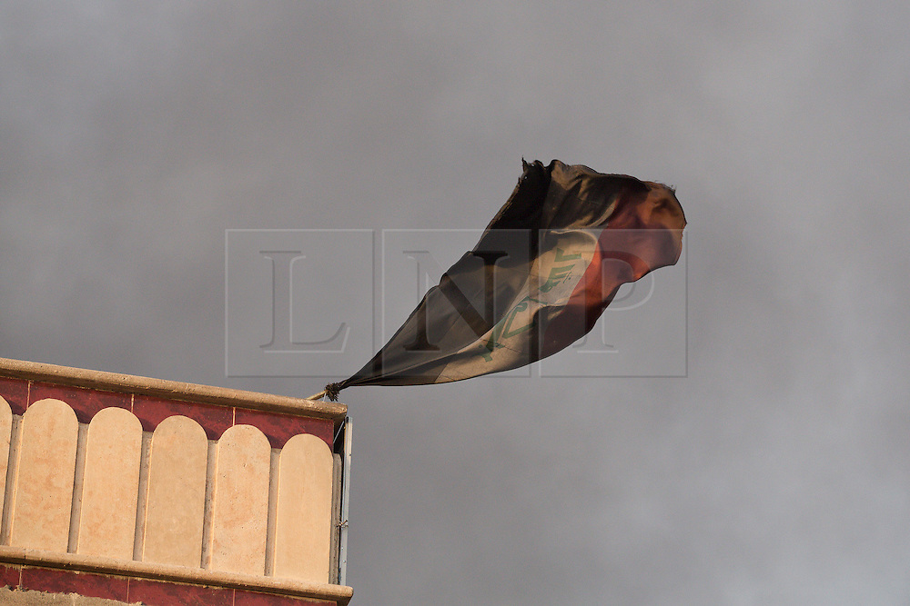 Licensed to London News Pictures. 02/11/2016. Qayyarah, Iraq. Blacked by the smoke from nearby burning oil wells, set alight by retreating Islamic State militants, the Iraqi flag flies from a building in the town of Qayyarah, Iraq.<br /> <br /> Two months after being liberated from the Islamic State, the Iraqi town of Qayyarah, located around 30km south of Mosul, is still dealing with the environmental repercussions of their ISIS occupation. The town's estimated 15,000 inhabitants constantly live under, and in, heavy clouds of smoke which often envelope the settlement. The clouds emanate from burning oil wells in a nearby oil field that were set alight by retreating ISIS extremists after a two year occupation. The proximity of the fires, often right next to homes within the town, covers many buildings and residents with thick soot and will lead to long term health and environmental implications. Photo credit: Matt Cetti-Roberts/LNP