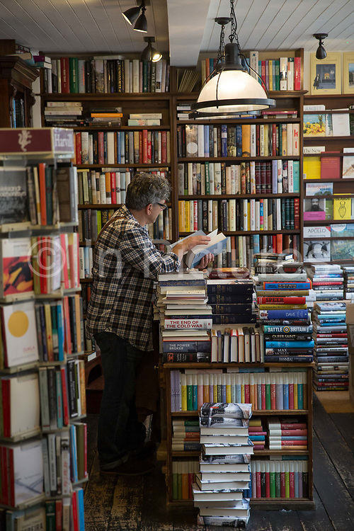 A man reading a book in John Sandoe bookshop on 19th October 2015 in London, United Kingdom. Independent bookshop since 1957, crammed with thousands of fiction, non-fiction and classic titles