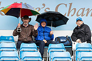 Yorkshire spectators take cover under umbrellas as they await the start of play ahead of the opening day of the Specsavers County Champ Div 1 match between Yorkshire County Cricket Club and Hampshire County Cricket Club at Headingley Stadium, Headingley, United Kingdom on 27 May 2019.