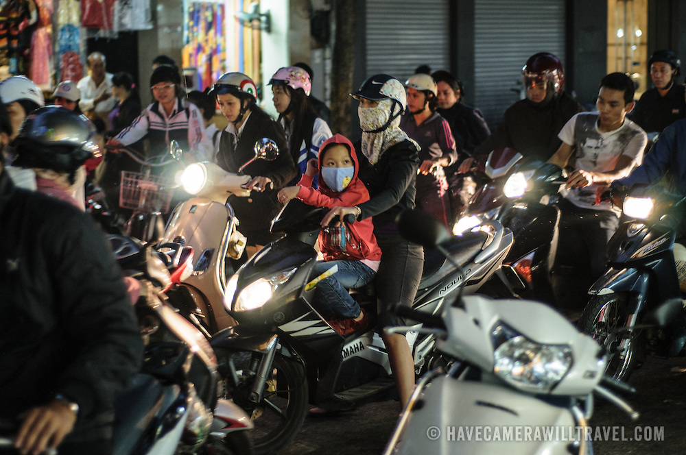 People on scooters negotiate the hectic traffic of Hanoi's Old Quarter at night.