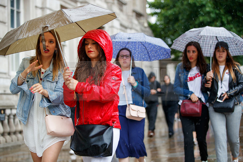 © Licensed to London News Pictures. 27/06/2017. London, UK. People take shelter from the rain on Whitehall in London on Tuesday, 27 June 2017. Photo credit: Tolga Akmen/LNP