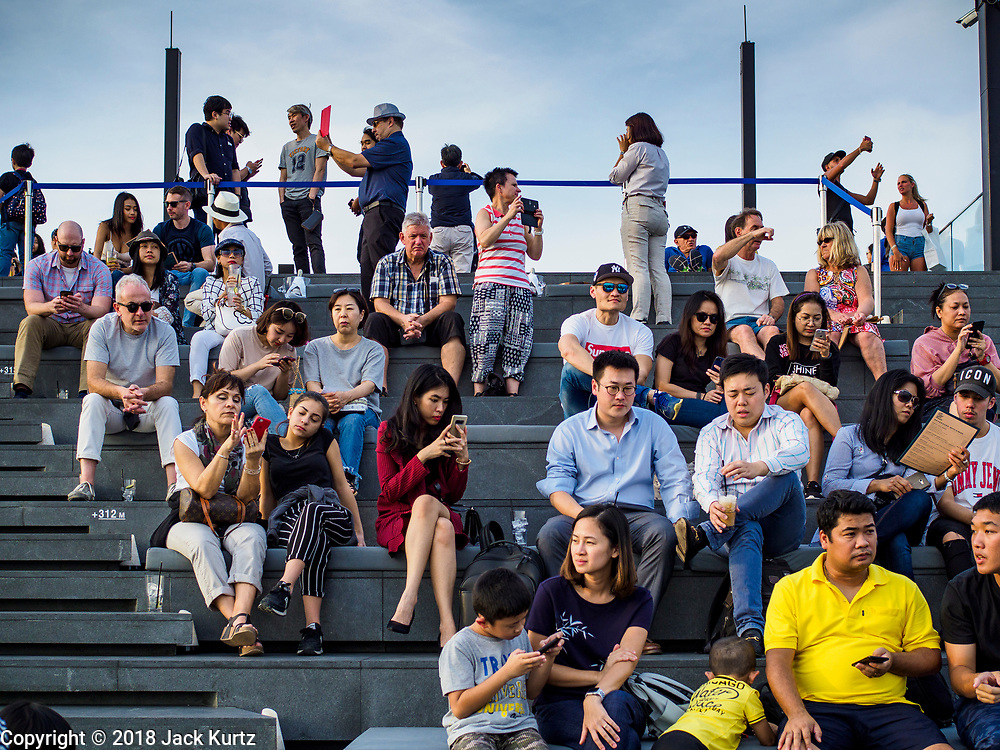 27 DECEMBER 2018 - BANGKOK, THAILAND:  People wait for the sunset on the observation deck of the King Power Maha Nakhon Tower. The MahaNakhon Skywalk, at the top of the King Power Maha Nakhon Tower, is  1,030 feet (314 meters) above street level. It is the tallest building and highest vantage point in Bangkok. The skywalk opened in November and has been drawing large crowds.     PHOTO BY JACK KURTZ