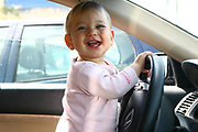 Smiling young girl of two drives a car