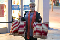 © Licensed to London News Pictures. 2/122/2020. Sheffield, UK.  A shopper wearing a face mask while holding shopping bags poses for a picture outside a Primark store  as shops re-open, following a national lockdown.Photo credit: Ioannis Alexopoulos/LNP