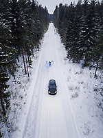 Aerial view of a man lighting a blue smoke grenade on a snowy road in the forest in Estonia.