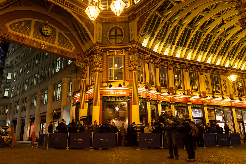 Tourists take photos and look around at the illuminated Leadenhall Market as city workers enjoy Friday night drinks in the Lamb Tavern, London, UK Friday January 5th 2018