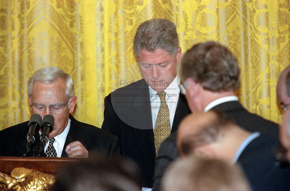 US President Bill Clinton bows his head in prayer at the annual prayer breakfast in the White House's East Room September 11, 1998 in Washington, DC. Reading from notes as his hushed audience of more than 100 ministers, priests and other religious leaders listened, the president said he had a broken spirit but still hoped to redeem the nation's trust.