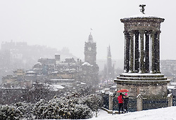 Snow falls on city of Edinburgh in December. Skyline view of city from Calton Hill, Scotland, UK.