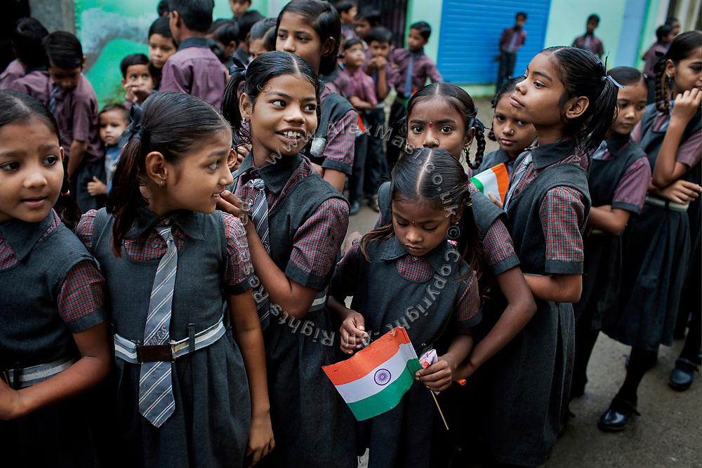 For India's Independence Day, Poonam, 10, (third from left) her sister Jyoti, 11, (third from right) and the pupils attending their cozy, private school are celebrating along the streets of Oriya Basti, one of the water-contaminated colonies in Bhopal, central India, near the abandoned Union Carbide (now DOW Chemical) industrial complex, site of the infamous '1984 Gas Disaster'.
