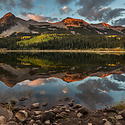 A still morning as sunrise hits the Beckwith Peaks at Lost Lake Slough in the Gunnison National Forest near Kebler Pass, Colorado.