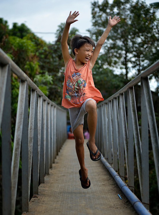 A boy waves happily as he walks across a foot bridge in the Suburban neighborhood of Rodriguez, Rizal, in the Philippines. Most of the community's families were relocated here from other area of Manila and the nearby countryside to make way for urban renewal projects or to move them out of harm's way. Yet the new community was hit hard by Typhoon Ketsana in 2009, and Christian Aid, a member of the ACT Alliance, provided emergency relief supplies. Over the years since, with help from Christian Aid and other groups, community members have organized themselves and engaged in a process of disaster risk reduction, including identifying and mapping high-risk zones and evacuation routes in their area. Christian Aid has also assisted with financial and technical support for income generating livelihood projects and community enterprises.