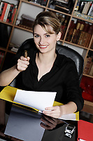cute and smiling businesswoman at the office desk pointing his pen as his finger at you