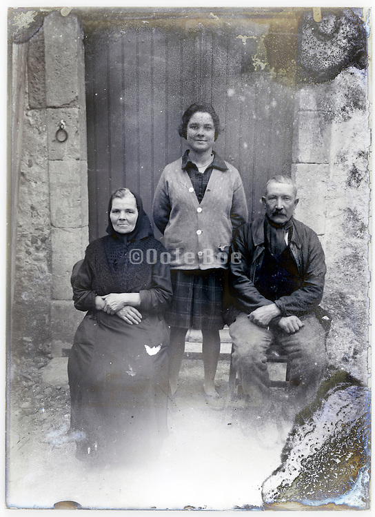 adult daughter posing with elderly parents early 1900s