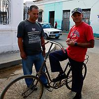 Central America, Cuba, Remedios. Cuban men and an unusual bike in Remedios.