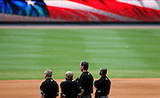 """ATLANTA - AUGUST 29:  Umpires (from left to right) Mike Everitt #57, Adrian Johnson #80, Tim McClelland #36 and Alan Porter #64 pause for a singing of """"God Bless America"""" during the game between the Atlanta Braves and the Florida Marlins at Turner Field on August 29, 2010 in Atlanta, Georgia.  The Braves beat the Marlins 7-6.  (Photo by Mike Zarrilli/Getty Images)"""